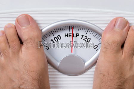 mans feet on weight scale indicating