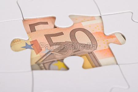 euro banknote versteckt unter jigsaw
