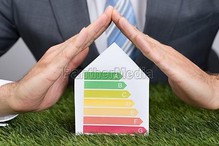geschaeftsmann abschirmung energieverbrauch etikett auf gras