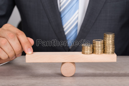 businessman balancing coins on wooden seesaw