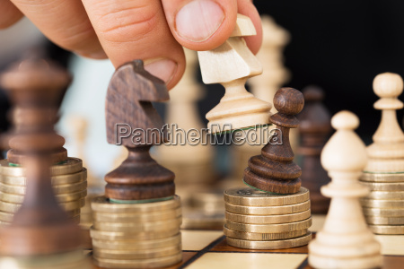 hand spielen schach gestapelt auf muenzen