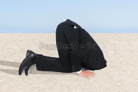 imprenditore nascondendo la testa in sabbia
