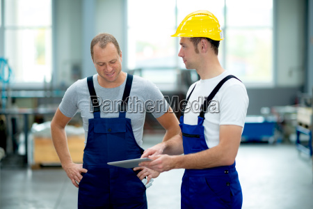 two worker in factory using tablet