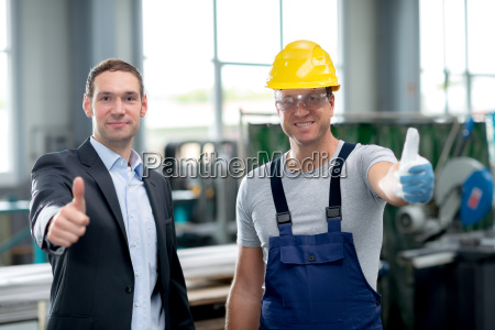 team in factory with thumbs up