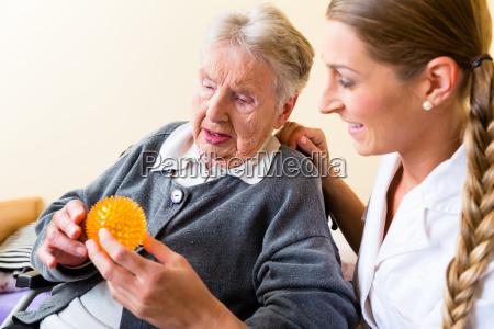altenpflegerin gibt physiotherapie an seniorin