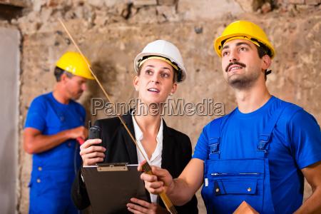 architektin und bauarbeiter auf baustelle diskutieren