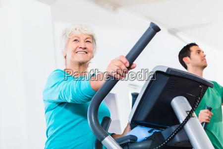seniorin auf eliptical trainer macht sport