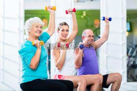 senioren und trainer mit hanteln bei