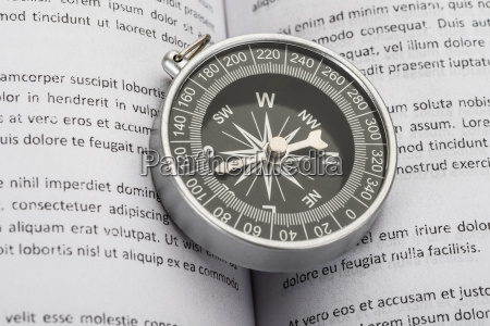 close up of compass on book
