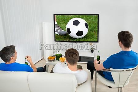 drei maenner vor dem fussball spiel