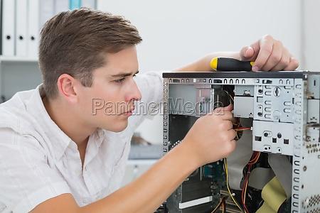 junge techniker auf defekten computer arbeiten