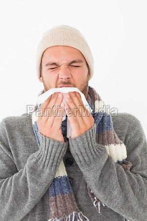 junger mann in warme kleidung niesen