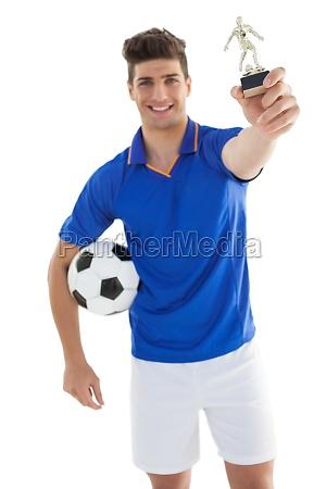 fussballspieler haelt sieger trophaee