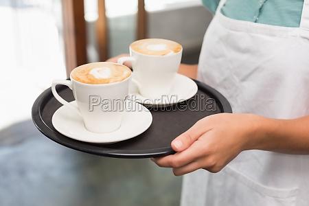 kellnerin haelt tablett mit cappuccinos