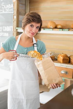 huebsche kellnerin croissant in papiertuete setzen