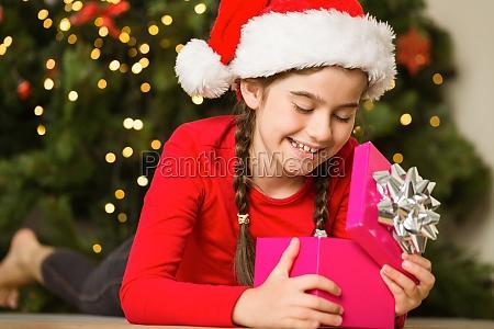 kleines maedchen das ein geschenk oeffnet