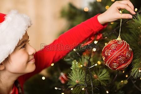 festliche kleines maedchen mit einem weihnachtsschmuck
