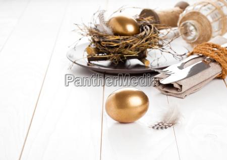 goldene ei tischdekoration auf weissem holzuntergrund
