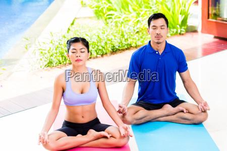 asiatische yoga paar in lotus sitz