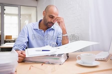 muede geschaeftsmann mit papierkram am schreibtisch