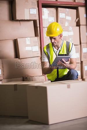 lagerarbeiter mit digitalen tablet im lager