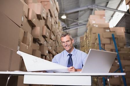 lagerleiter mit blaupause und laptop