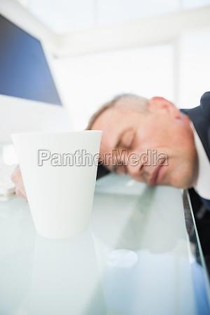 erschoepft geschaeftsmann schlaeft bei der arbeit