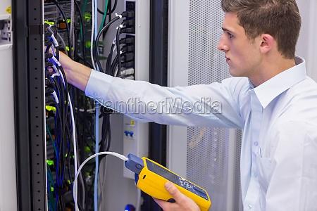 serioeser techniker mit digitalem kabelanalysator auf
