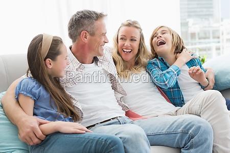 laechelnde eltern und kinder sitzen zusammen