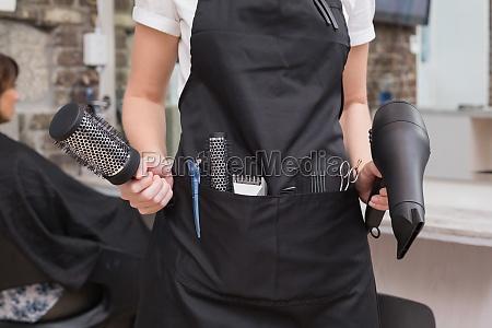 friseur holding pinsel und haartrockner