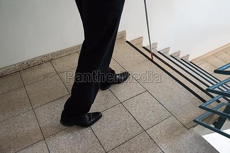 blind man walking near stairway