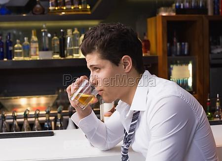 junger mann trinkt whisky ordentlich