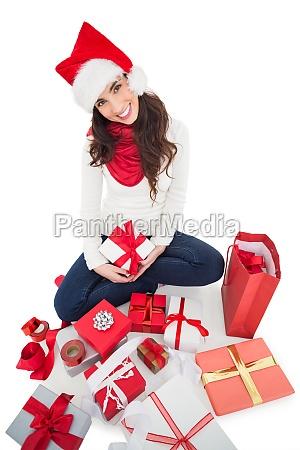 festliche bruenette sitzt und verpackt weihnachtsgeschenke