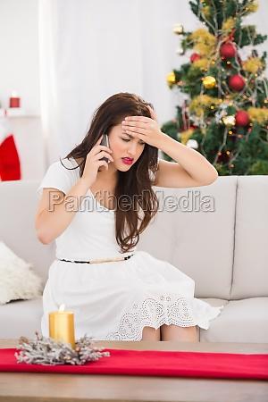 konzentrierte bruenette am telefon am weihnachtstag