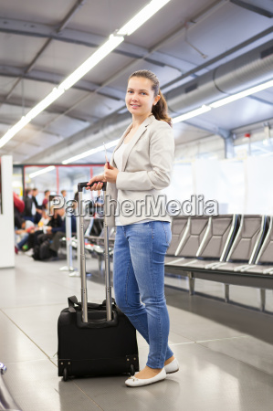businesswoman with luggage at airport lobby