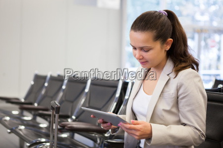 businesswoman using digital tablet at airport