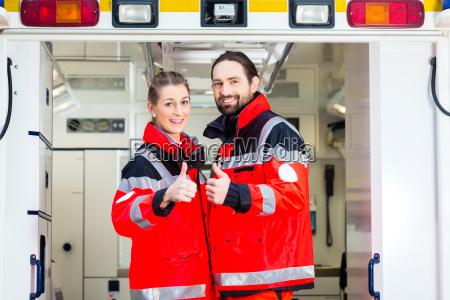 notartzt und sanitaeter vor krankenwagen