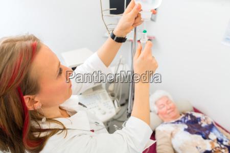 doktor legt klinik seniorin einen tropf