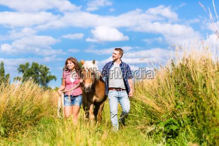 paar fuehrt pferd durch wiese im
