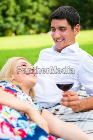 paar trinkt rotwein im gras in