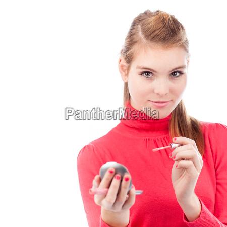 huebsche junge frau die anwendung lipgloss