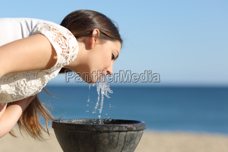 woman drinking water from a fountain