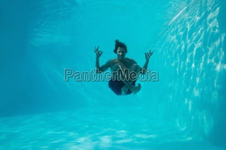 junger mann unter wasser schwimmen