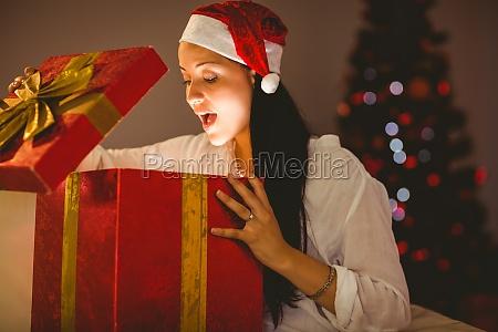 festliche bruenette eroeffnet ein gluehendes weihnachtsgeschenk