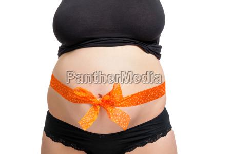 junge schwangere frau mit orangener schleife