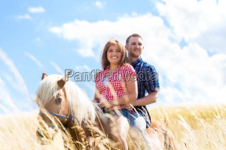 paar reitet auf pferd in sommer