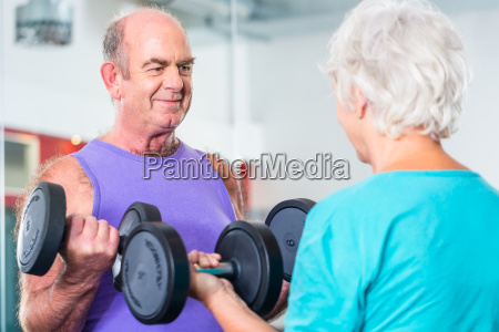 senior couple with dumbbells in fitness