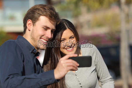 happy couple watching media in a