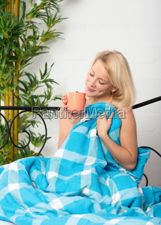 young woman drinking coffee in bed