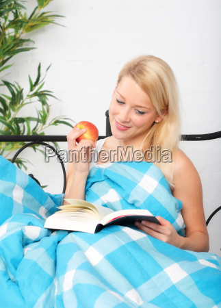 woman reading in bed reading a